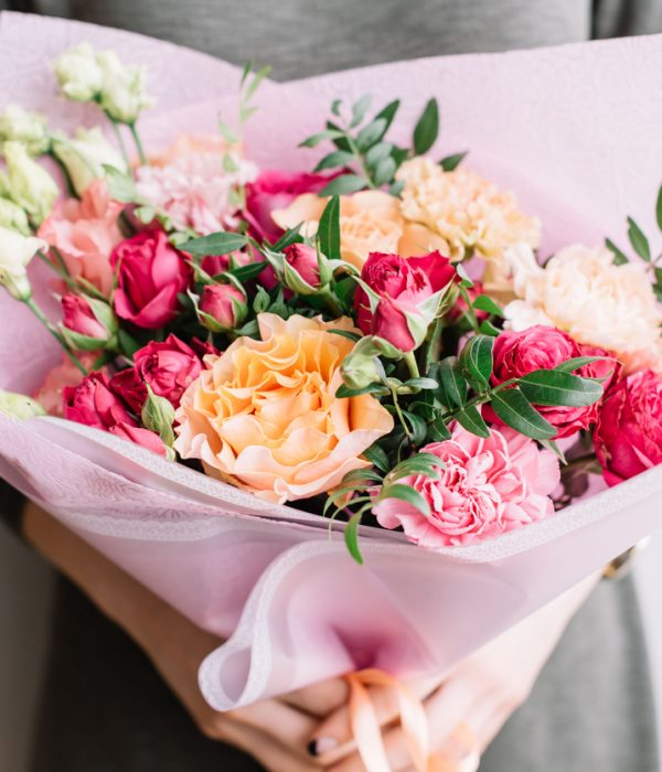 Very nice young woman holding a colourful fresh blossoming flower bouquet of different sorts of roses, carnations, eustoma, peonies on the grey wall background